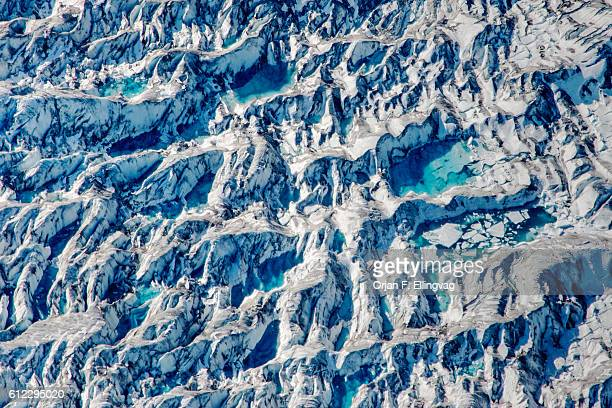Ponds of water from melting ice at the Knik Glacier in Alaska Lack of snowcover expose the ash fallout from the nearby Redoubt Volcano reducing the...