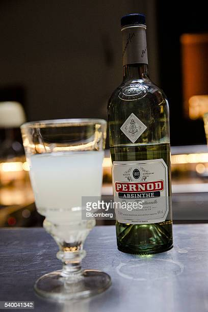 A pontarlier glass of absinthe stands on a bar at Pernod Ricard SA's absinthe distillery in Thuir France on Tuesday June 7 2016 The potent green...