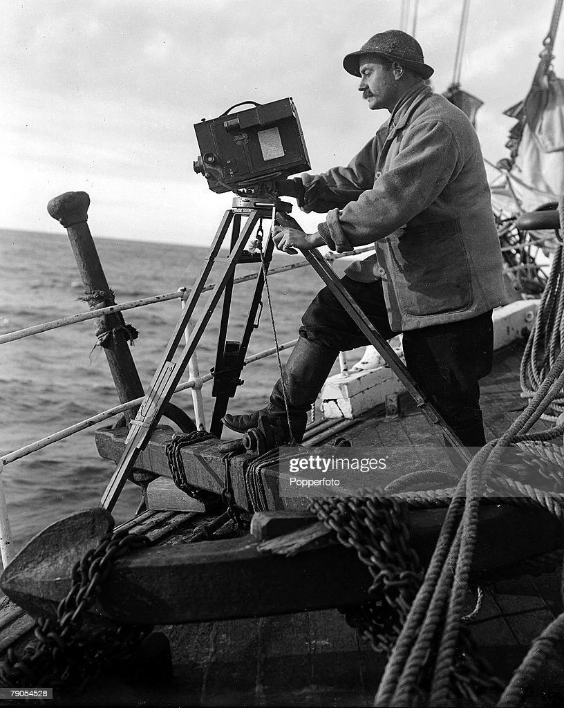 H,G Ponting, Captain Scott+s Antarctic Expedition 1910 - 1912, Photographer Herbert Ponting taking a picture of whales with his camera over the side of the Terra Nova ship