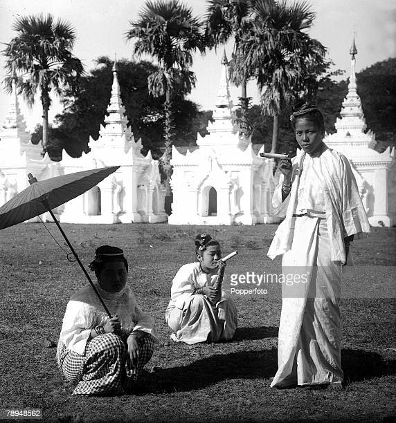 HG Ponting in Asia 1900 1906 Burma A Native girl in traditional dress stands smoking a cheroot with two other girls crouching next to her one holding...
