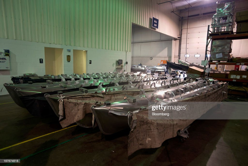 Pontoons wait to have flooring and carpet installed on the assembly line at the Nautic Global Group production facility in Elkhart, Indiana, U.S., on Tuesday, Dec 4, 2012. The U.S. Census Bureau is scheduled to release factory orders data on Dec. 5. Photographer: Ty Wright/Bloomberg via Getty Images