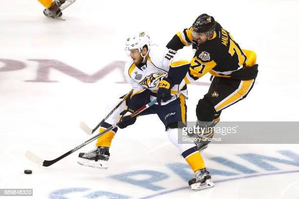 Pontus Aberg of the Nashville Predators controls the puck against Evgeni Malkin of the Pittsburgh Penguins during the first period in Game One of the...