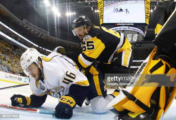 Pontus Aberg of the Nashville Predators falls to the ice against Ron Hainsey of the Pittsburgh Penguins in Game Two of the 2017 NHL Stanley Cup Final...