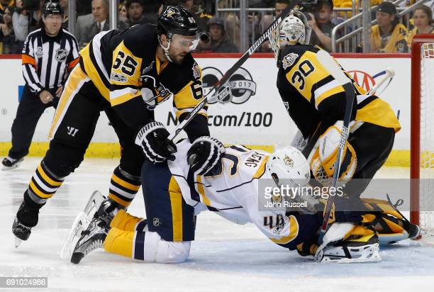 Pontus Aberg of the Nashville Predators is shoved into goaltender Matt Murray of the Pittsburgh Penguins by Ron Hainsey during the third period of...