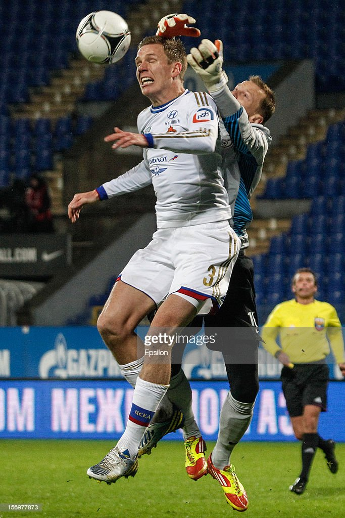 Pontus Wernbloom (L) of PFC CSKA Moscow vies for the header with Vyacheslav Malafeev of FC Zenit St. Petersburg during the Russian Football League Championship match between FC Zenit St. Petersburg and PFC CSKA Moscow at the Petrovsky Stadium on November 26, 2012 in St. Petersburg, Russia.