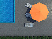 High resolution 3d render of an Hotel swimming pool with beach-umbrella and three lounge-chairs in straight topview.