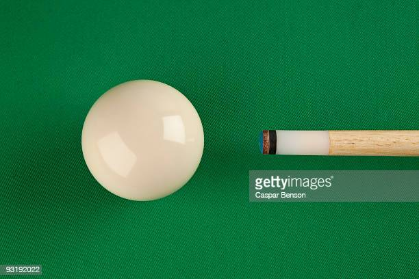 A pool cue and a cue ball on a pool table