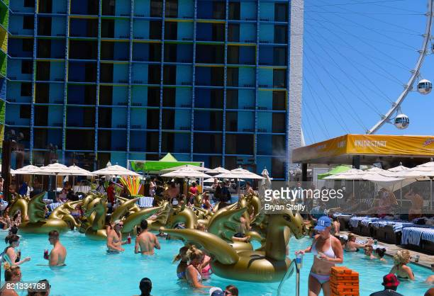 Pool goers ride inflatable dragons during DJ/actor Kristian Nairn's performance at The LINQ Hotel Casino on July 23 2017 in Las Vegas Nevada