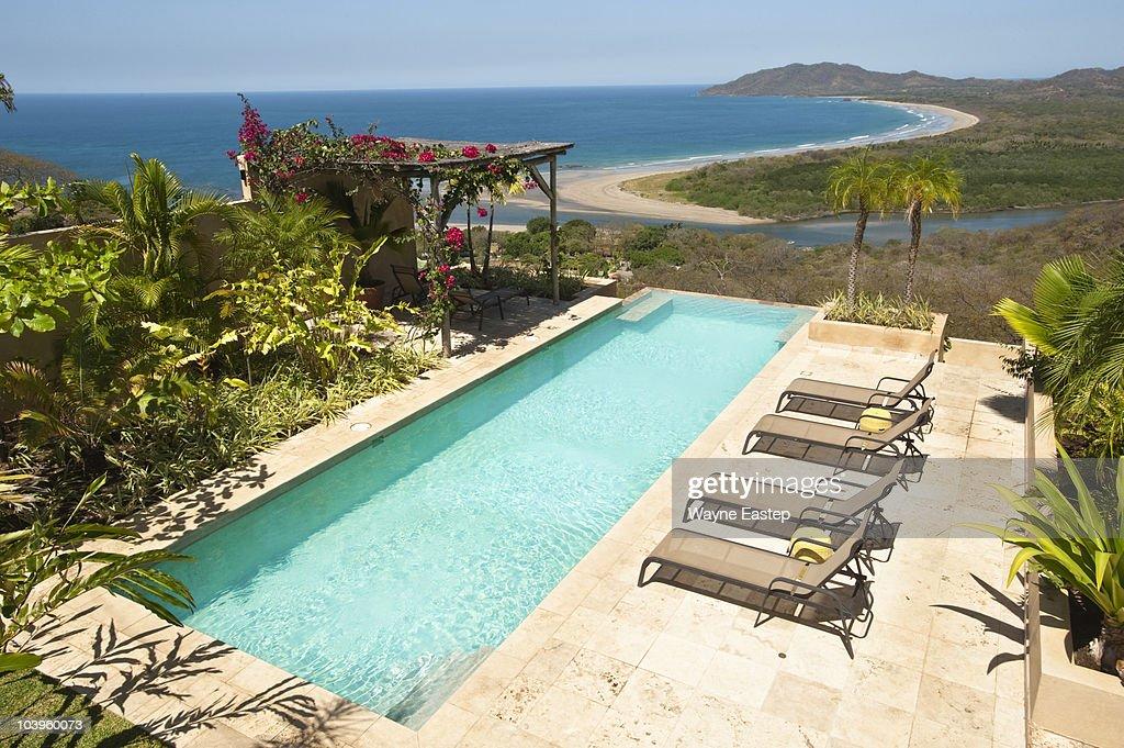 pool lounge chairs gazebo overlooking beach