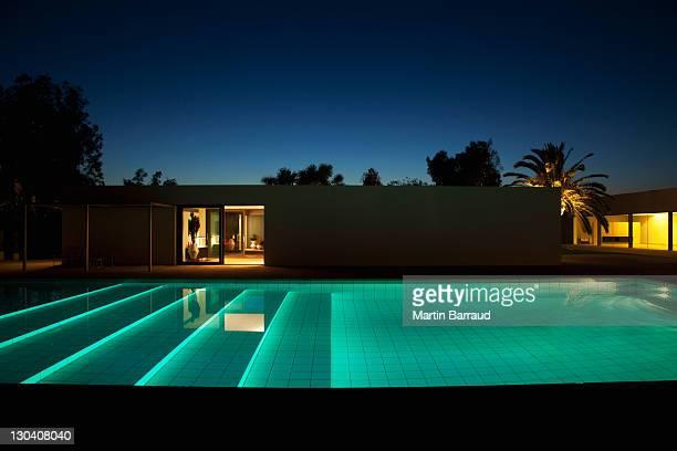 La piscine à l'extérieur de la maison moderne au crépuscule