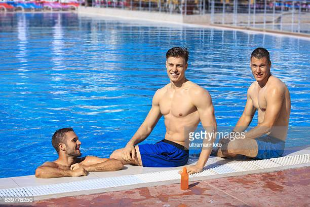 Pool party   Friends  Three young man relaxing at swimming pool