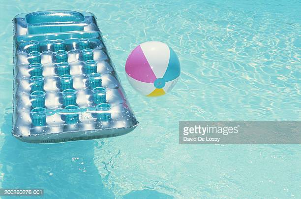 Pool raft and ball floating on swimming pool