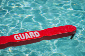 A close up shot of a life guards red rescue tube floating in a pool.