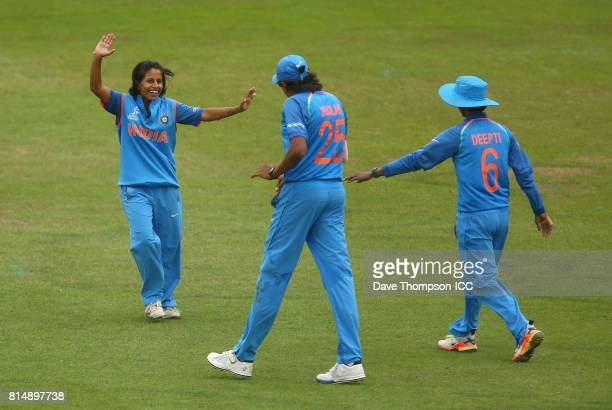 Poonam Yadav of India celebrates with Jhulan Goswami of India and Deepti Sharma of India after taking the wicket of Maddy Green of New Zealand during...