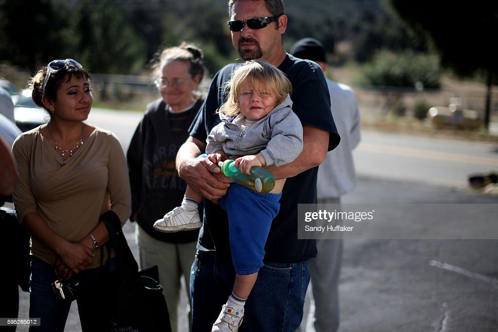 Poor and elderly citizens wait in line to receive donated food items from a Feeding America truck on Thursday November 3 2011 in Descanso California...
