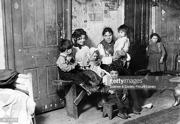 Poor European immigrants possibly Italians in a slum dwelling One of the children has calipers on his leg Photograph taken by Lewis Wickes Hine...
