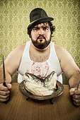 poor fat man eating fish head soup at wood table