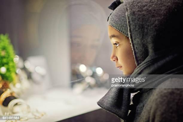 Poor girl is looking sad a jewelry store window