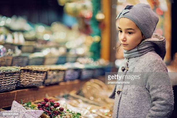 Poor, little girl is standing sad at the Christmas market