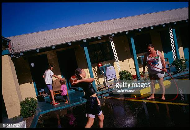 A poor mother and her children play with a garden hose to cool off outside their small motel room home Poor families pay rent by the month in one of...