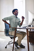 Shot of a young designer suffering from back pain while working at his desk in an office