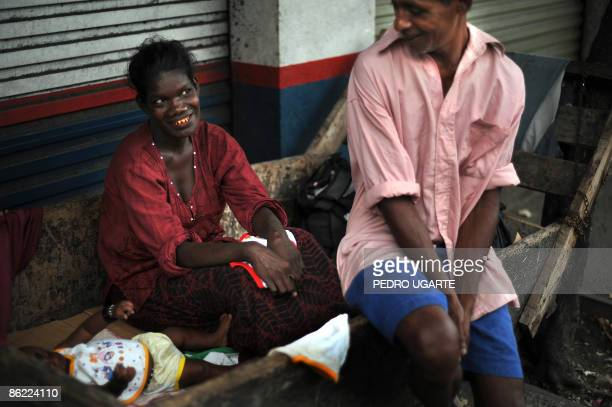A poor Sri Lankan family uses a wooden chariot as a bed for their baby in Colombo on April 26 2009 The central bank said beginning of April that...