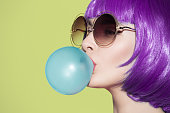 Pop art woman portrait wearing purple wig. Blow a blue bubble chewing gum. Olive background.