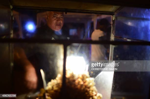 A pop corn seller looks watches the the BrazilianFrench 'Planeta Ginga' film and music free festival at the Cidade de Deus shantytown in Rio de...
