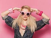 Pop girl portrait wearing odd sunglasses and posing