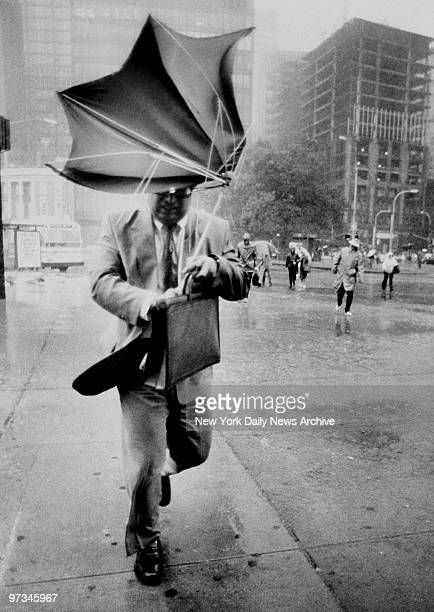 Pop goes the umbrella as pedestrian struggles against a headwind in lower Manhattan during the first stages of Hurricane Gloria