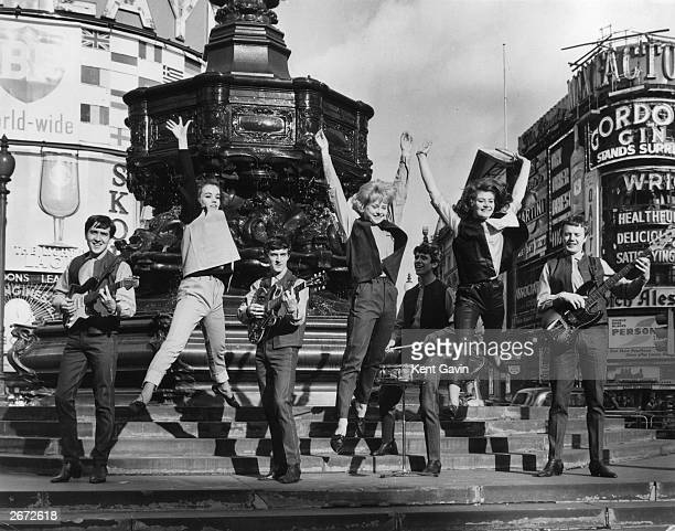 Pop group 'Swinging Blue Jeans' playing on the steps of Eros in Piccadilly London for a group of models From left to right Pat Robinson wearing ice...