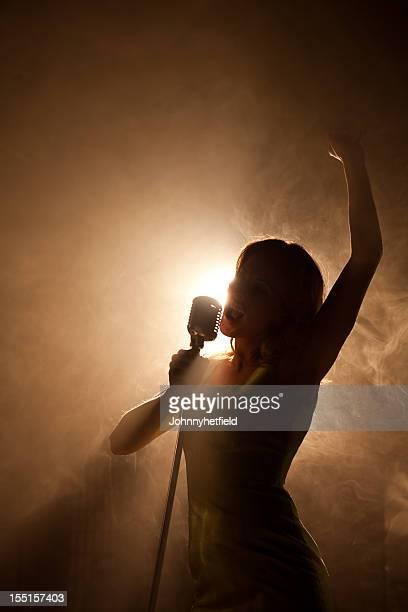 Pop idol backlit with microphone on the big stage