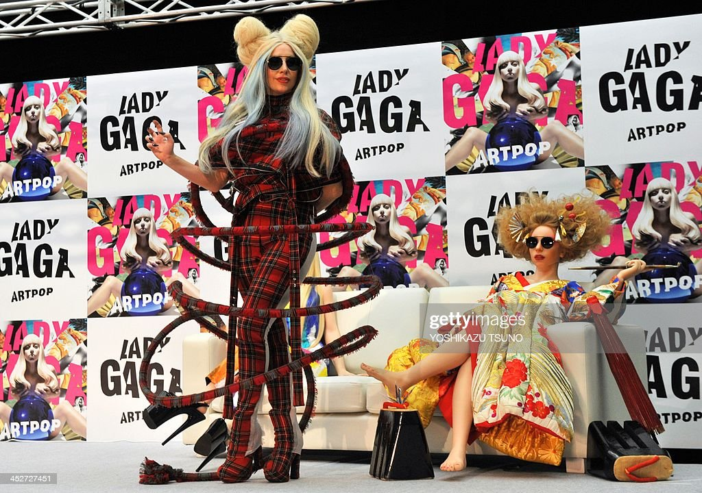 US pop music star Lady Gaga (L) poses next to her look-alike doll called 'Gagadoll' made of silicon during a press conference in Tokyo on December 1, 2013. Lady Gaga is in here for the promotion of her latest album 'ARTPOP'. AFP PHOTO / Yoshikazu TSUNO