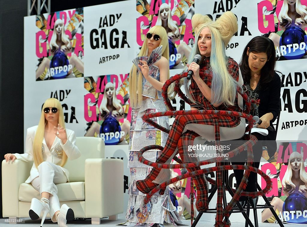 US pop music star Lady Gaga (2nd-R) poses next to her look-alike doll called 'Gagadoll' made of silicon during a press conference in Tokyo on December 1, 2013. Lady Gaga is in here for the promotion of her latest album 'ARTPOP'. AFP PHOTO / Yoshikazu TSUNO