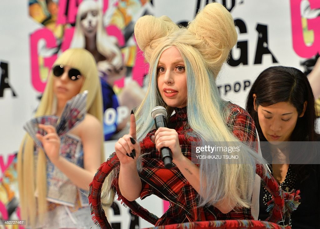 US pop music star Lady Gaga (C) poses next to her look-alike doll called 'Gagadoll' made of silicon during a press conference in Tokyo on December 1, 2013. Lady Gaga is in here for the promotion of her latest album 'ARTPOP'. AFP PHOTO / Yoshikazu TSUNO