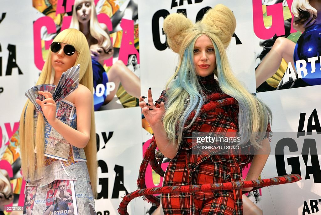 US pop music star Lady Gaga (R) poses next to her look-alike doll called 'Gagadoll' made of silicon during a press conference in Tokyo on December 1, 2013. Lady Gaga is in here for the promotion of her latest album 'ARTPOP'. AFP PHOTO / Yoshikazu TSUNO
