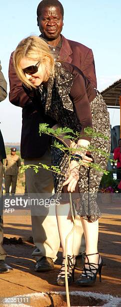 US pop queen Madonna holds a Moringa tree soon after planting it during a ceremony to officially launch the construction work of Madonna's Raising...