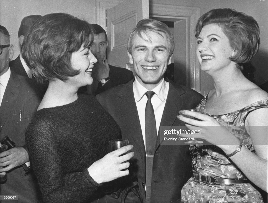 Pop singer and actor Adam Faith (1940 - 2003) enjoys himself at a party with Jo Gray and Joan Francis.