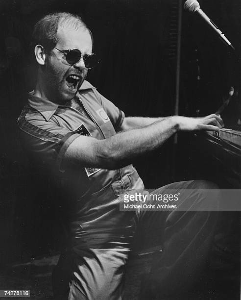 Pop singer Elton John performs in a jumpsuit at the piano in circa 1973