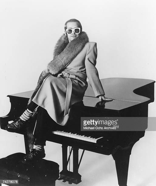 Pop singer Elton John poses for a portrait sitting on top of a piano wearing a furlined coat in circa 1974