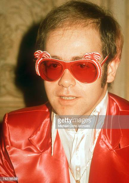 Pop singer Elton John poses for a portrait wearing a shiny red jacket and matching sunglasses in circa 1975