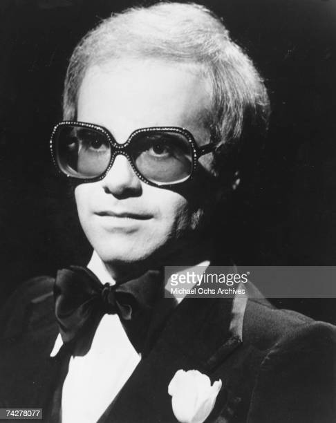 Pop singer Elton John poses for a portrait wearing glasses and a bow tie in circa 1973