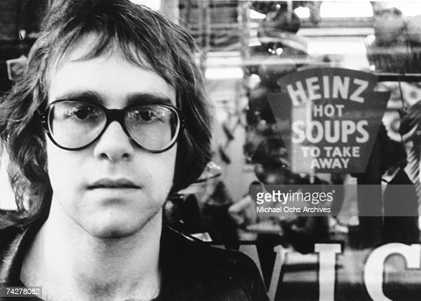 Pop singer Elton John poses for a portrait wearing glasses in front of a sign that says 'Heinz Hot Soups' in circa 1970