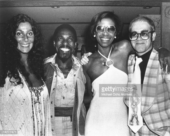 Pop singer Elton John poses for a portrait with with fellow popular singers Cher Al Wilson and Natalie Cole at a Wings concert at the Forum in June...