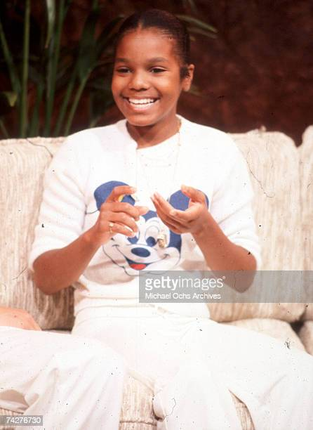 Pop singer Janet Jackson giggles as she sits on a couch wearing a Mickey Mouse tshirt in circa 1977
