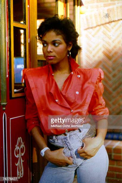 Pop singer Janet Jackson poses for a portrait session leaning against a popcorn cart in August 1985 in Los Angeles California