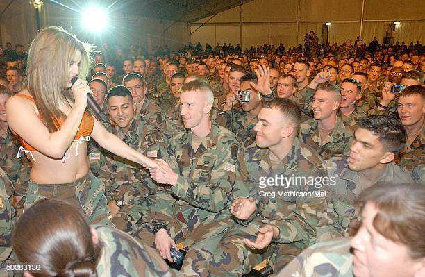 Pop singer Jessica Simpson wearing a top made from a parachute entertaining US Army paratroops as part of the USO Holiday Tour