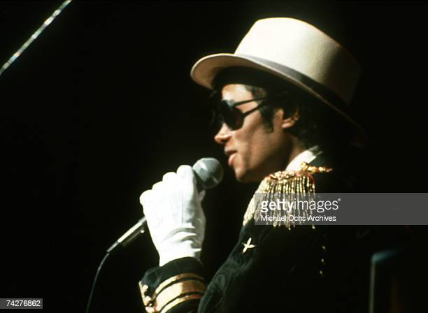 Pop singer Michael Jackson performs onstage wearing a military style jacket white hat sunglasses and a white glove in 1984