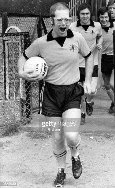 Pop singer pianist and football club chairman Elton John leads Watford Football Club team out onto the pitch