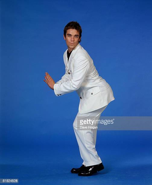 Pop singer Robbie Williams member of boy band Take That posing against a bright blue background he is wearing a white suit mid 1990s